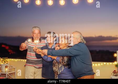Gerne ältere Freunde feiern Geburtstag mit WUNDERKERZEN Sterne Outdoor - Ältere Menschen Spaß in Terrasse im Sommer Nächte - Stockfoto