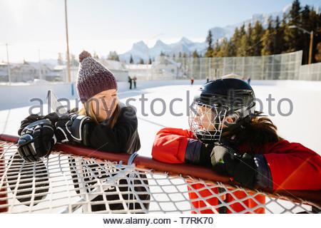 Glückliche Mutter und Tochter spielen Im freien Eishockey, eine Pause am Ziel - Stockfoto