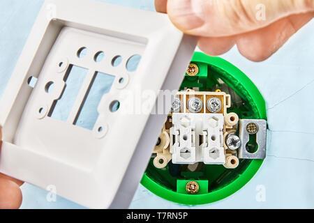 Worker ist, Teil der Europäischen drücken Sie die Taste auf dem runden Schaltkasten, elektrische Installation arbeiten. - Stockfoto