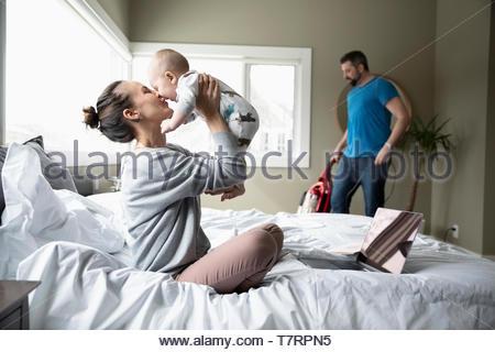 Liebevolle Mutter spielt mit Baby Sohn am Bett, während Ehemann Vakuum im Hintergrund - Stockfoto