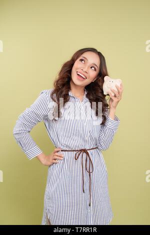 Sparschwein Einsparungen glücklich lächelnde Frau. Weibchen mit rosa Sparschwein isoliert auf weißem Hintergrund. - Stockfoto