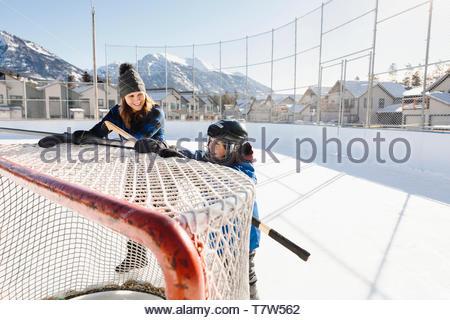 Mutter und Sohn drücken outdoor Eishockey Ziel - Stockfoto