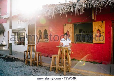 Junge männliche Touristen Sidewalk Cafe arbeiten, Mexiko - Stockfoto