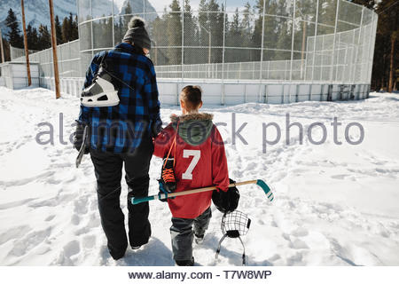 Mutter und Sohn gehen mit Outdoor Eishockey Ausrüstung - Stockfoto
