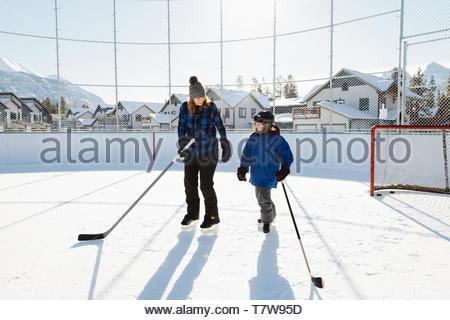 Mutter und Sohn spielen Im freien Eishockey - Stockfoto
