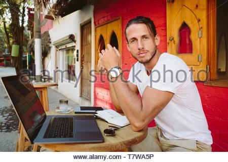 Portrait selbstbewussten jungen männlichen Touristen am Laptop zu Sidewalk Cafe arbeiten, Mexiko - Stockfoto