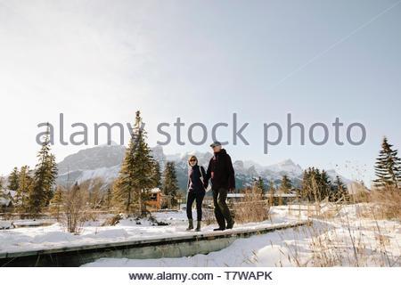 Senior Paar entlang sonnigen, verschneiten Weg mit Bergen im Hintergrund - Stockfoto