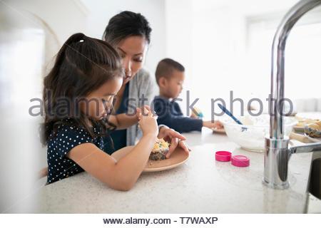 Mutter und Kinder dekorieren Cupcakes in der Küche - Stockfoto
