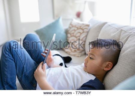 Junge mit digital-Tablette auf Sofa im Wohnzimmer - Stockfoto