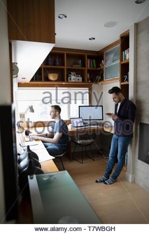 Männliche homosexuelle Paare von zu Hause aus arbeiten, mit Laptop und Smartphone im Home Office - Stockfoto