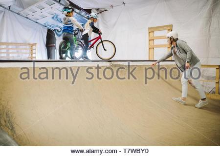 Mutter führt Kinder auf bmx Fahrräder an der Rampe bei indoor Skatepark - Stockfoto