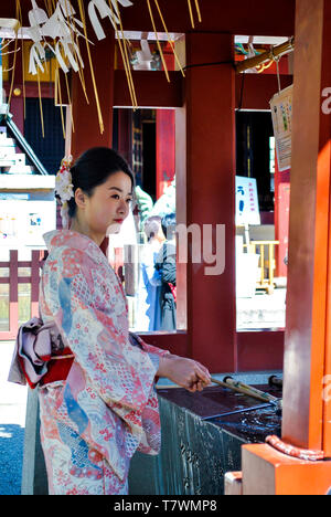 Eine Frau, die zeremonielle Reinigung Ritus in der chōzuya oder temizuya. Sensō-ji Temple. Asakusa, Tokyo, Japan. - Stockfoto
