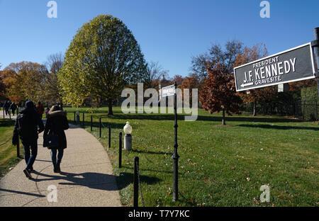 Richtung Zeichen der Präsident J. F. Kennedy gravesite mit Besuchern im Hintergrund in Arlington National Cemetery. Arlington. Virginia. USA - Stockfoto
