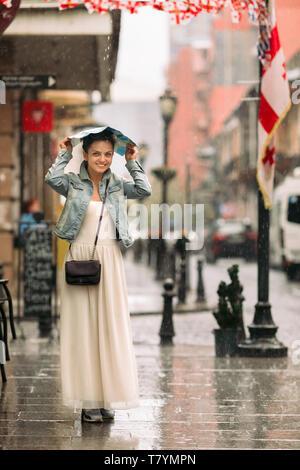 Attraktive Frau im Kleid mit Karte Spaziergänge durch die Straßen der Altstadt an regnerischen Tag - Stockfoto