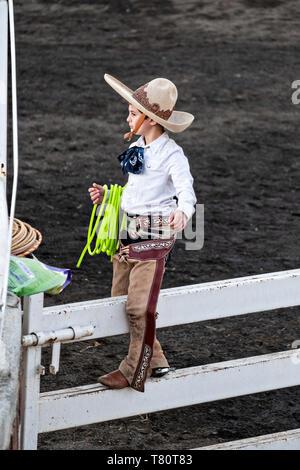 Der Achtjährige Juan Franco, von der legendären Franco Familie von Charro Champions, wartet auf einem Zaun während einer Übung in der jalisco Hochland Stadt Capilla de Guadalupe, Mexiko. Die roping Ereignis aufgerufen Manganas eine Torte oder Abseilen zu Fuß und beinhaltet eine Charro zu Fuß roping eine wilde Stute durch seine Vorderbeine zu veranlassen, wenn Rolle. Die wilde Stute ist gejagt um den Ring durch drei montiert Charros. - Stockfoto