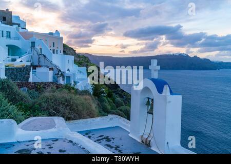 Blick auf die weiß gekalkten Häuser und Glockenturm in Oia, Santorini, Griechenland, in der Dämmerung - Stockfoto