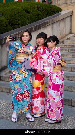 Junge japanische Frauen, gekleidet in farbenprächtige Kimonos selfies in Kyoto, Japan, Asien - Stockfoto