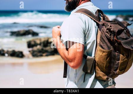 In der Nähe von erwachsenen Menschen kaukasischen Mann reisen mit Leder style Rucksack - alternative traveler Urlaub Outdoor Konzept und Strand Meer im Hintergrund - Stockfoto