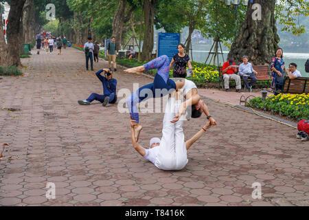 Ein junges Paar Akrobatik auf dem Gehsteig auf der Seite der Hoan Kiem See in der Altstadt von Hanoi, Vietnam, Südostasien - Stockfoto
