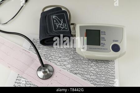 Moderne elektrische tonometer und ein Stethoskop auf einem elektrokardiogramm Chart. Haushalt Blutdruckmessgerät - Stockfoto