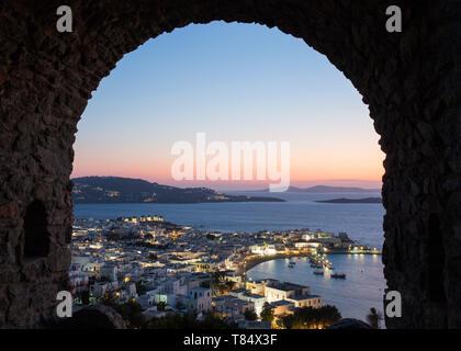 Mykonos Stadt, Mykonos, südliche Ägäis, Griechenland. Blick über die beleuchtete Stadt und Hafen durch steinernen Torbogen in das Schloss Stadtmauer, Dämmerung. - Stockfoto