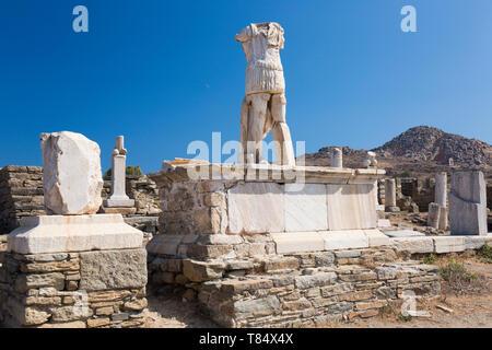 Delos, Mykonos, südliche Ägäis, Griechenland. Kopflose Statue steht man inmitten archäologische Überreste, Berg Kynthos im Hintergrund. - Stockfoto