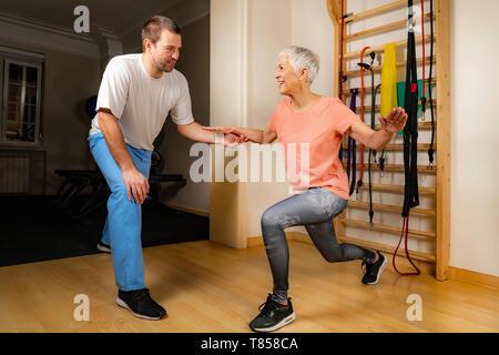 Ältere Frau Ausfallschritte machen - Stockfoto
