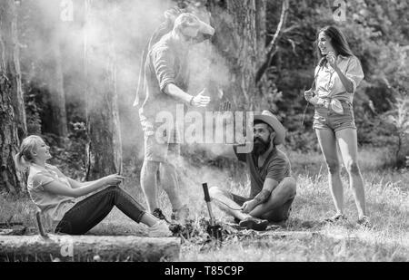 Melden Sie Sommer Picknick. Unternehmen Spaß beim braten Würstchen auf Sticks. Freunde treffen in der Nähe von Feuer zu hängen und gebratene Würstchen snacks Natur Hintergrund vorbereiten. Treffpunkt für die große Picknick. - Stockfoto