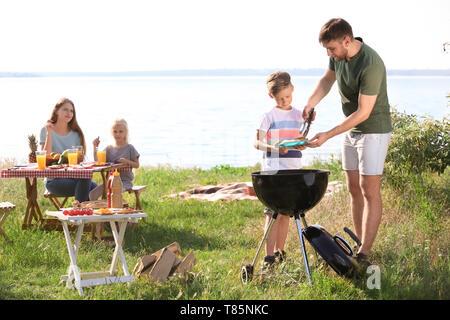 Junger Mann mit seinem Sohn in der Nähe von Grill im Freien. Familie Picknick - Stockfoto