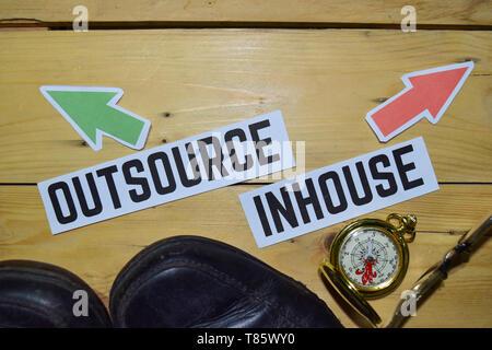 Auslagern oder Inhouse entgegengesetzte Richtung Schilder mit Stiefeln, Brillen und Kompass auf Holz vintage Hintergrund. Business, Bildung und Finanzen Konzepte - Stockfoto