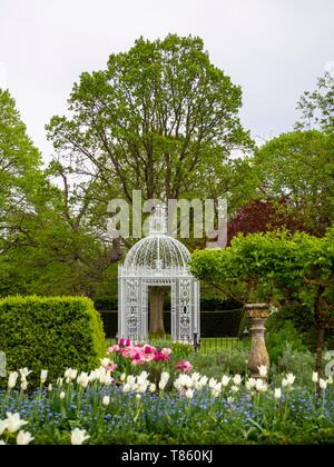 Weiße Pagode im Parterre an chenies Manor Gardens Anfang Mai mit Weißen tuilp Triumphator, formgehölze Bäume, Sonnenuhr und rosa Tulpen im Hochformat.