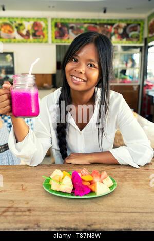 Frau mit Glas rosa Smoothie von dragon Obst im Glas. Gesunde vegane Lebensweise. - Stockfoto
