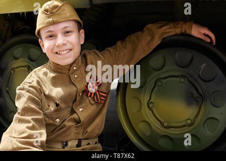 Junge gekleidet in der sowjetischen militärischen Uniform während des Zweiten Weltkrieges in der Nähe von Army Tank posing - Stockfoto