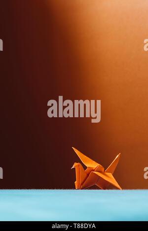 Orange origami Vogel, ein Vogel aus Papier - Origami. (Weichzeichner), auf hellen Stoff Kissen - Stockfoto