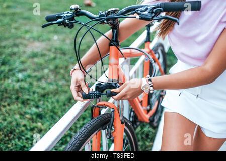 Close-up Mädchen Hand schloss mit digitalen Chiffre. Frau Sommer steht Fahrrad Fahrrad Verriegelung mit Kabel. Nimmt Password Lock, Diebstahl Fahrrad Parkplatz - Stockfoto