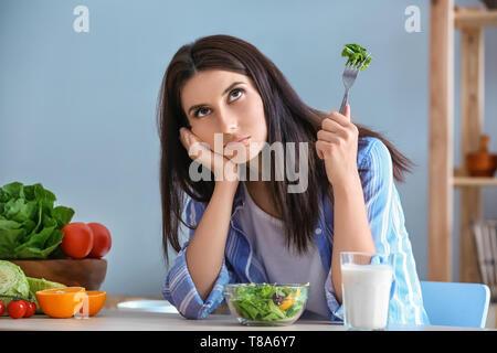 Zögern Frau gesund essen Salat mit Gemüse im Innenbereich. Diät Konzept - Stockfoto