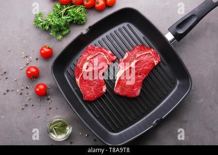 Grillpfanne mit rohem Fleisch, frische Gewürze, Tomaten und Öl auf Grau strukturierten Hintergrund - Stockfoto