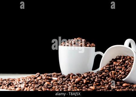In weiße Tasse schwarzen Kaffee und Kaffeebohnen auf schwarzem Hintergrund. Ansicht von oben, Platz für Text Stockfoto