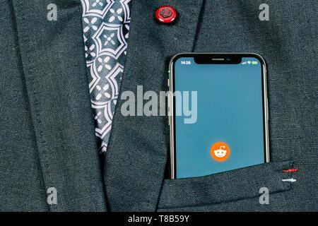Sankt-Petersburg, Russland, 24. August 2018: Reddit Symbol auf Apple iPhone X Bildschirm des Smartphones close-up in der Jackentasche. Reddit App Symbol. Rot - Stockfoto