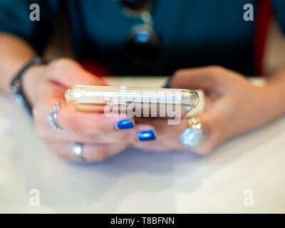 Close-up Woman's Hand mit blau Nägel und Ringe in Fingern mit Smartphone auf weißer Tisch. Menschen mit Technik Konzept. - Stockfoto