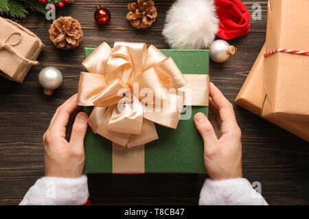 Santa Claus holding Geschenkbox auf Holztisch, Ansicht von oben - Stockfoto