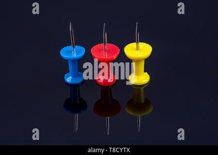 Drei Stifte in der Farbe Blau, Rot und Gelb auf schwarzem Hintergrund - Stockfoto
