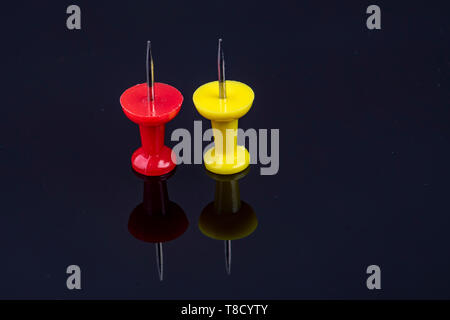 Die beiden Stifte in der Farbe Rot und Gelb auf schwarzem Hintergrund - Stockfoto