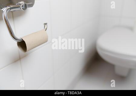 Horizontale selektiven Fokus auf leere Klopapierrolle in eine Toilette mit WC im Hintergrund - Stockfoto
