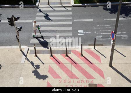 Reiter auf Stand-up Roller oder motorisierten Kick Scooter Reiten in Radweg oder Radweg mit Fahrbahnmarkierungen & Fußgängerüberweg Marseille Frankreich - Stockfoto