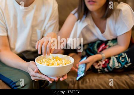 Frau Hände, Popcorn aus dem Abscheidegefäß watching Film mit Freund. - Stockfoto