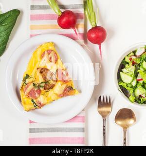 Omelette mit Croutons, Wurst, Käse und Dill in eine weiße Platte. In der Nähe von Salat aus Gurken, Kohl und Rettich - Stockfoto