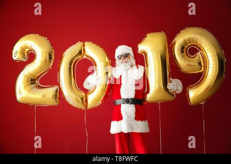 Portrait von Santa Claus mit Ballons in der Form von Zahlen 2019 auf farbigen Hintergrund - Stockfoto