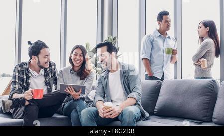 Kreative, Designer sitzen, entspannen Sie sich und sprechen auf Sofa im Büro. Tak eine Kaffeepause vom Arbeiten - Stockfoto