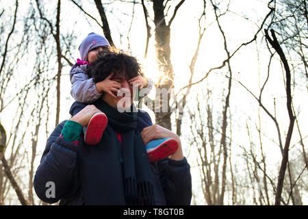 Junge Vati Baby auf seinen Schultern in einem Wald. Baby die Augen ihres Vaters für Spaß. - Stockfoto